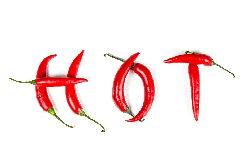 Word hot made from red chili peppers on white