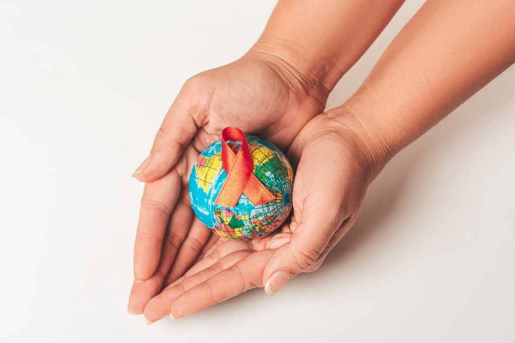 World Aids Day Concept. Hands holding globe with AID red ribbon