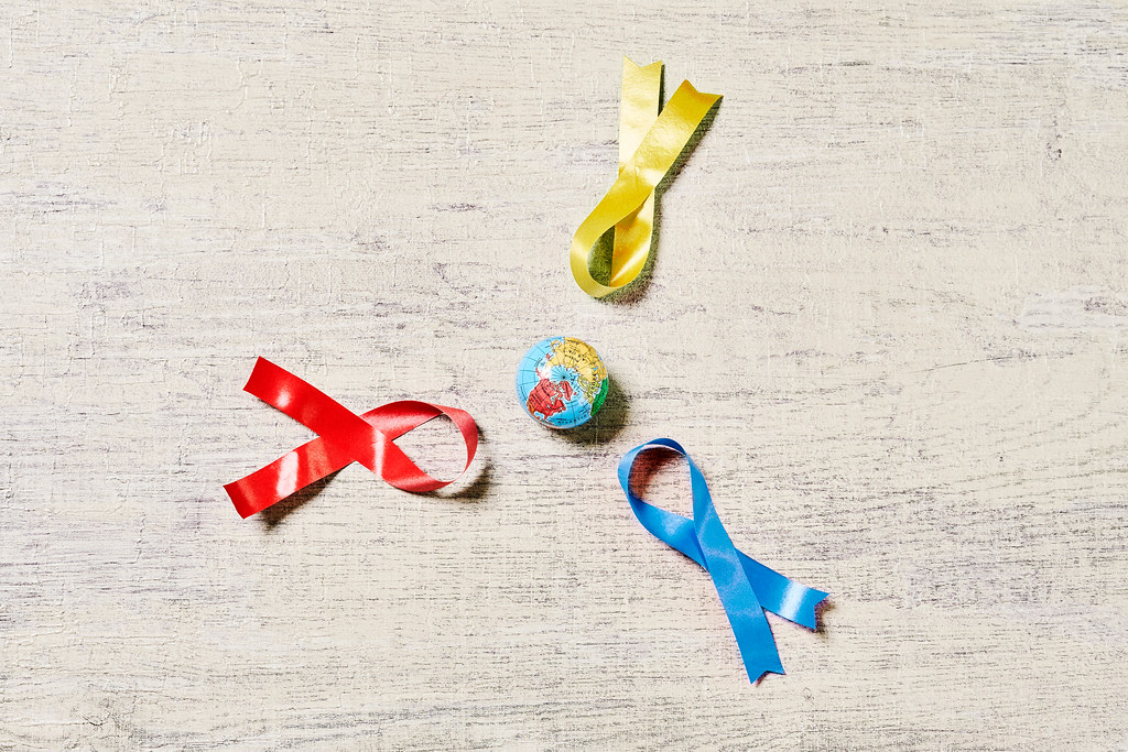 World cancer day concept with ribbons and globe on wooden desk