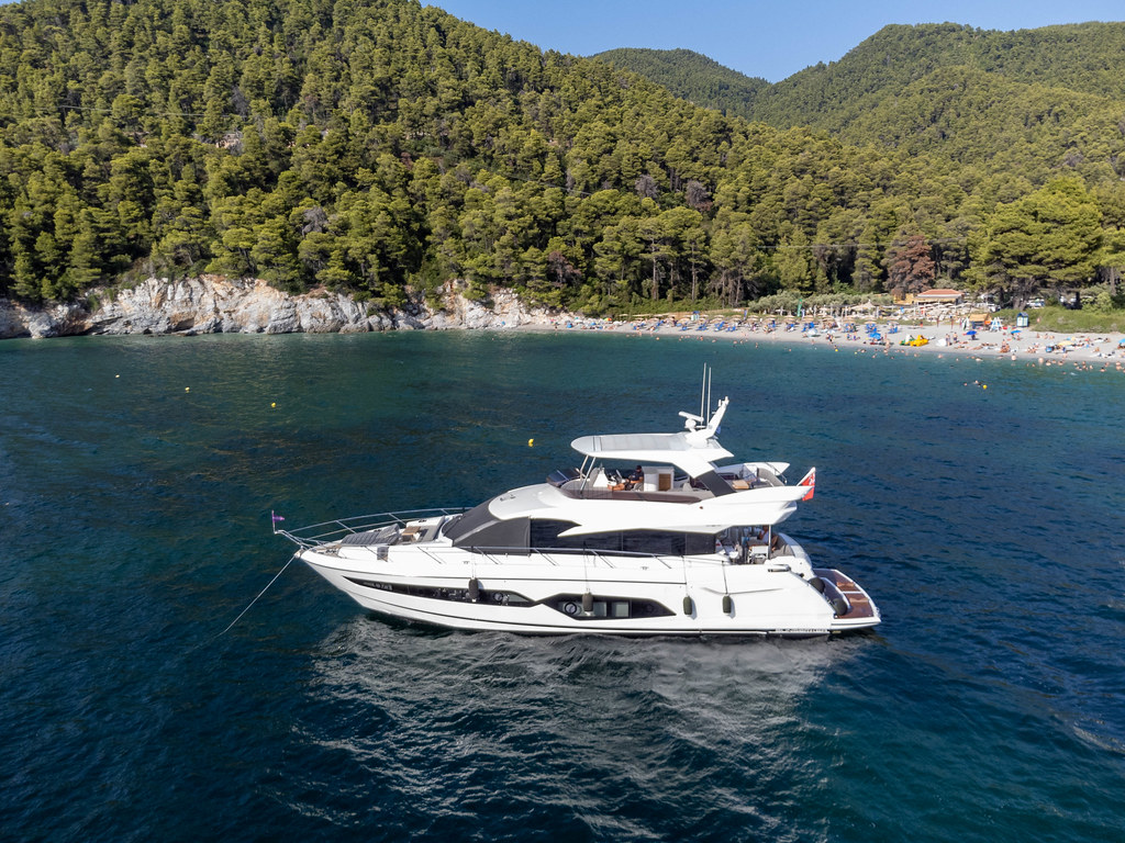Yacht off the coast of Skopelos in front of the crowded Kastani beach surrounded by wooded hills