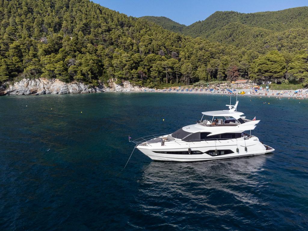 Yacht vor der Küste von Skopelos vor dem beliebten Kastani Strand, umgeben von bewaldeten Hügeln