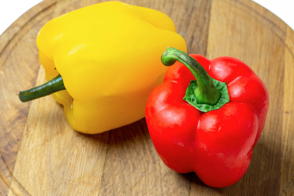 Yellow and red fresh bell peppers on a wooden kitchen board