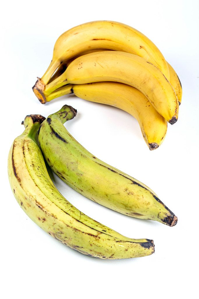 Yellow bananas and green plantain on white
