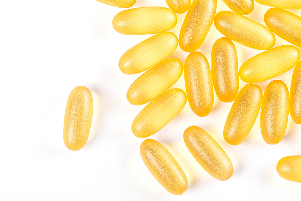 Yellow fish oil capsules on white background