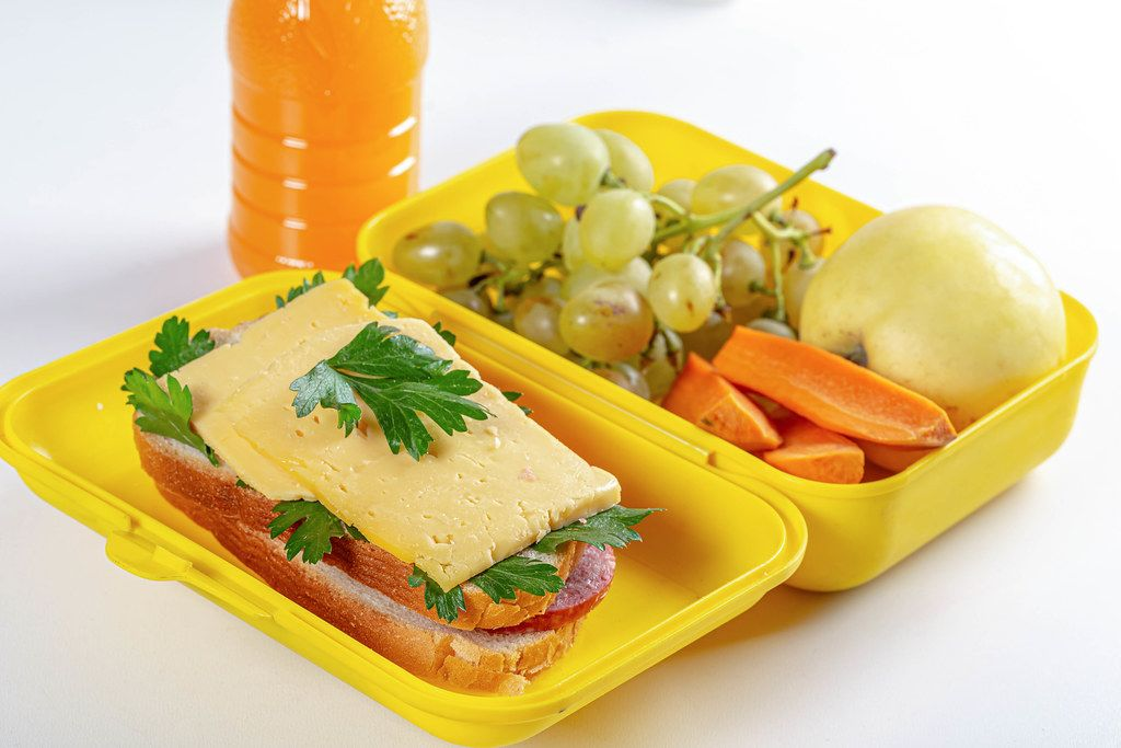 Yellow lunch box with lunch for a child at school