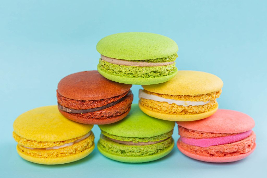Yellow, pink, green and brown macaroon cookies on a blue background