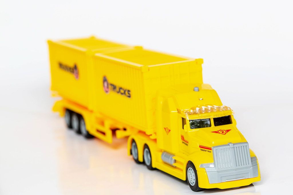 Yellow plastic toy car truck on white background