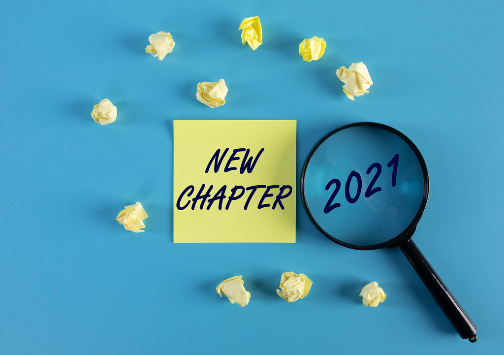 Yellow sticky note and magnifying glass with 2021 New Chapter text