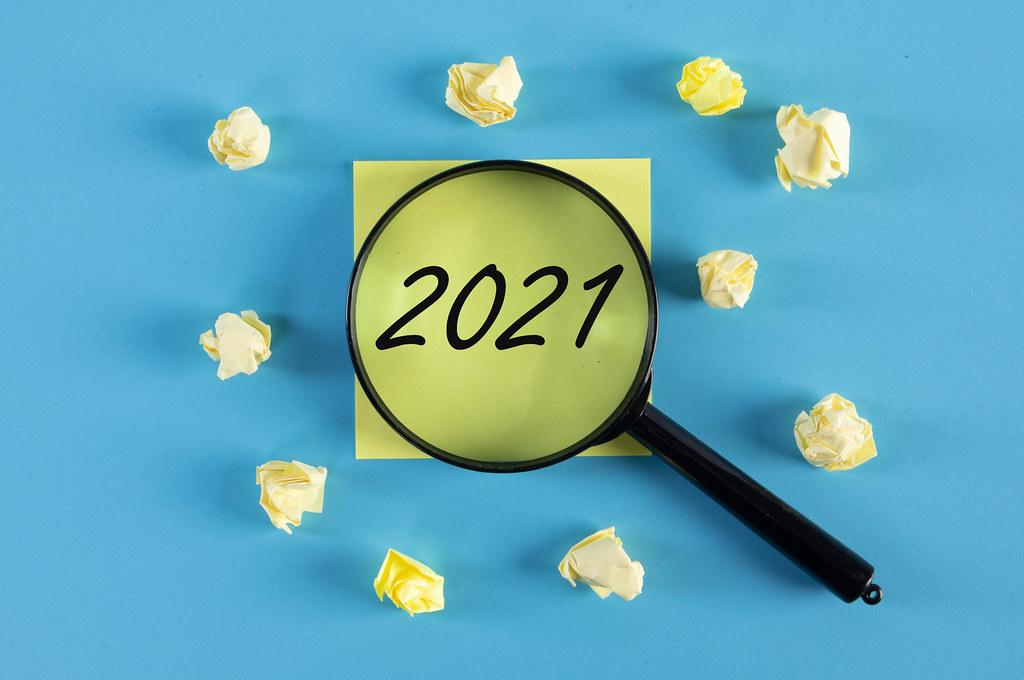 Yellow sticky note and magnifying glass with 2021 text