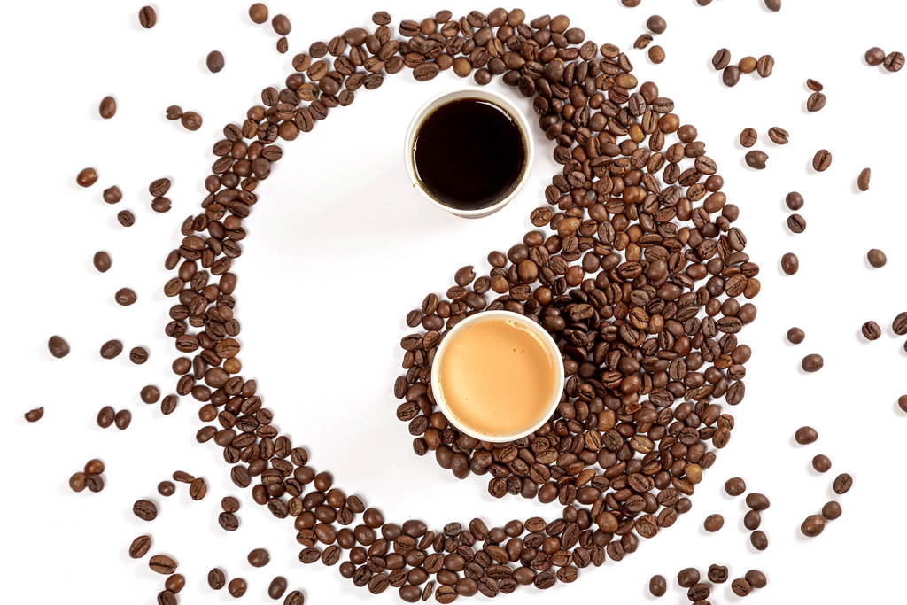Yin yang symbol made from roasted coffee beans, espresso and coffee with milk in paper cups