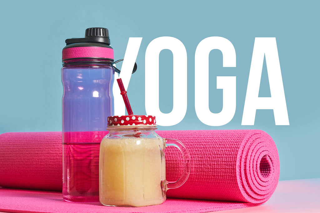 Yoga supplies - yoga mat, a bottle of water and fresh smoothie over blue background