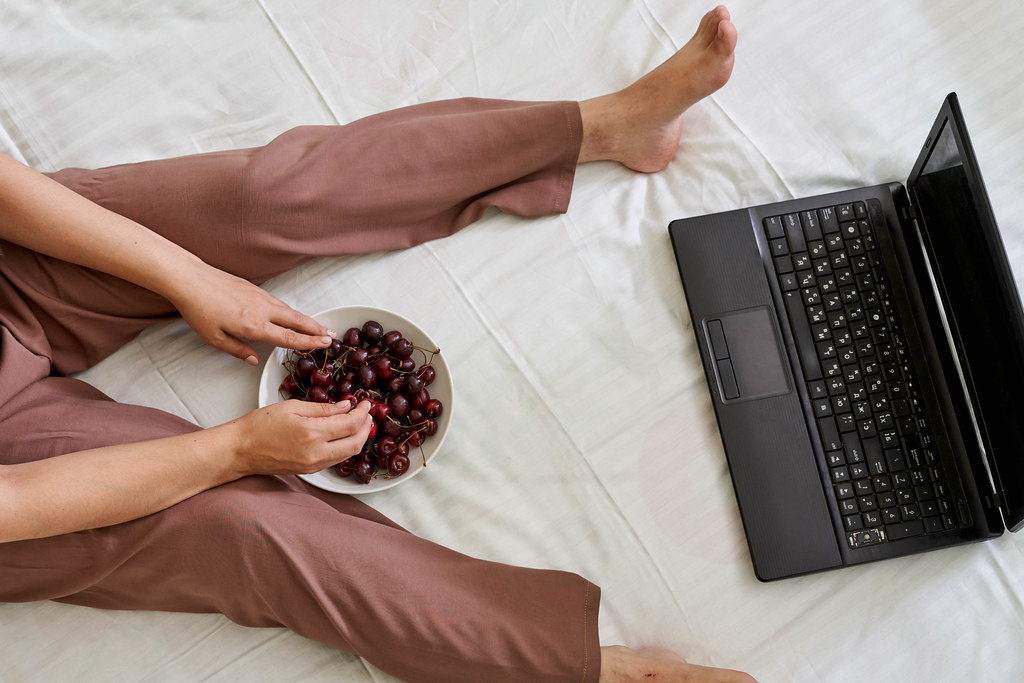 Young female eating fresh cherry fruits and watching movie on the laptop