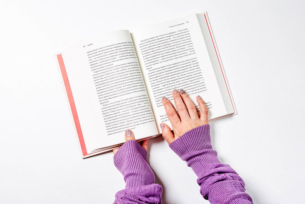 Young female in warm sweater reading a book