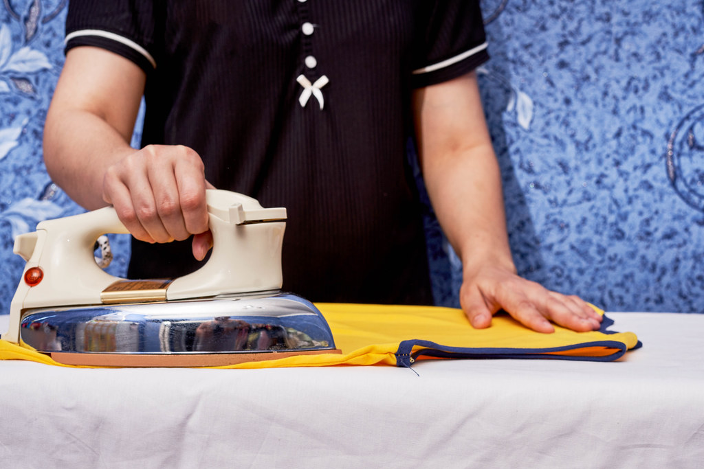 Young female ironing a cloth