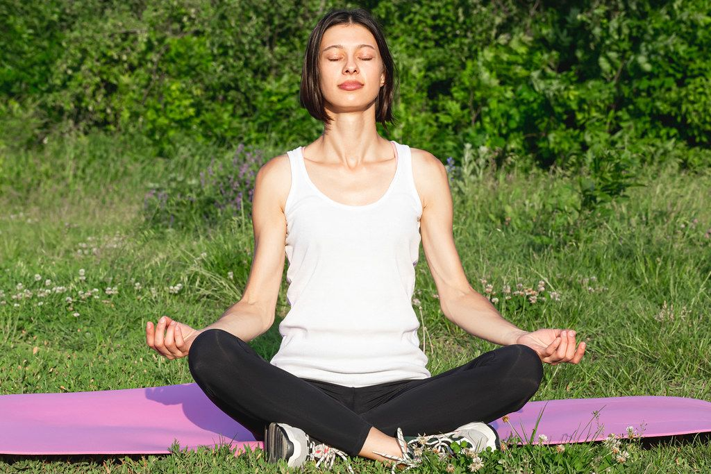 Young girl in Sukhasan pose meditates in nature