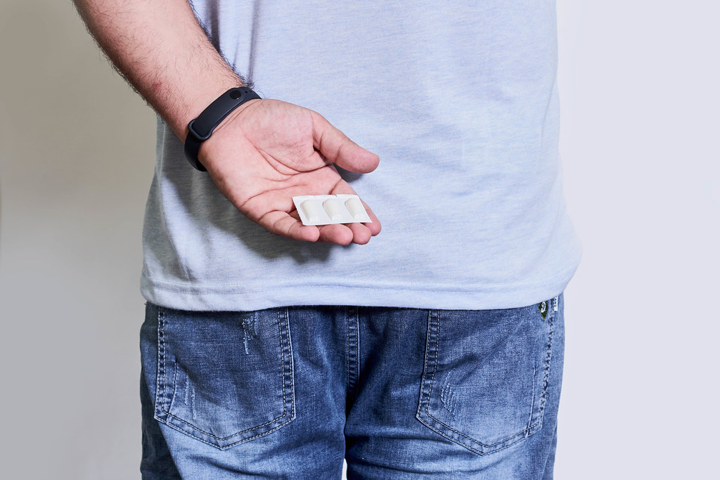 Young male suffering from hemorrhoids holds hemorrhoidal suppositories in hands