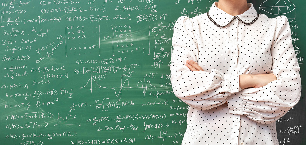 Young scientist standing over chalkboard filled with different scientific formulas