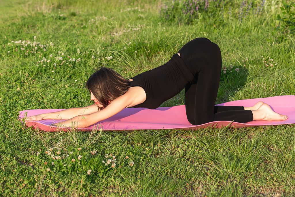 Young woman relaxes in a balasana pose