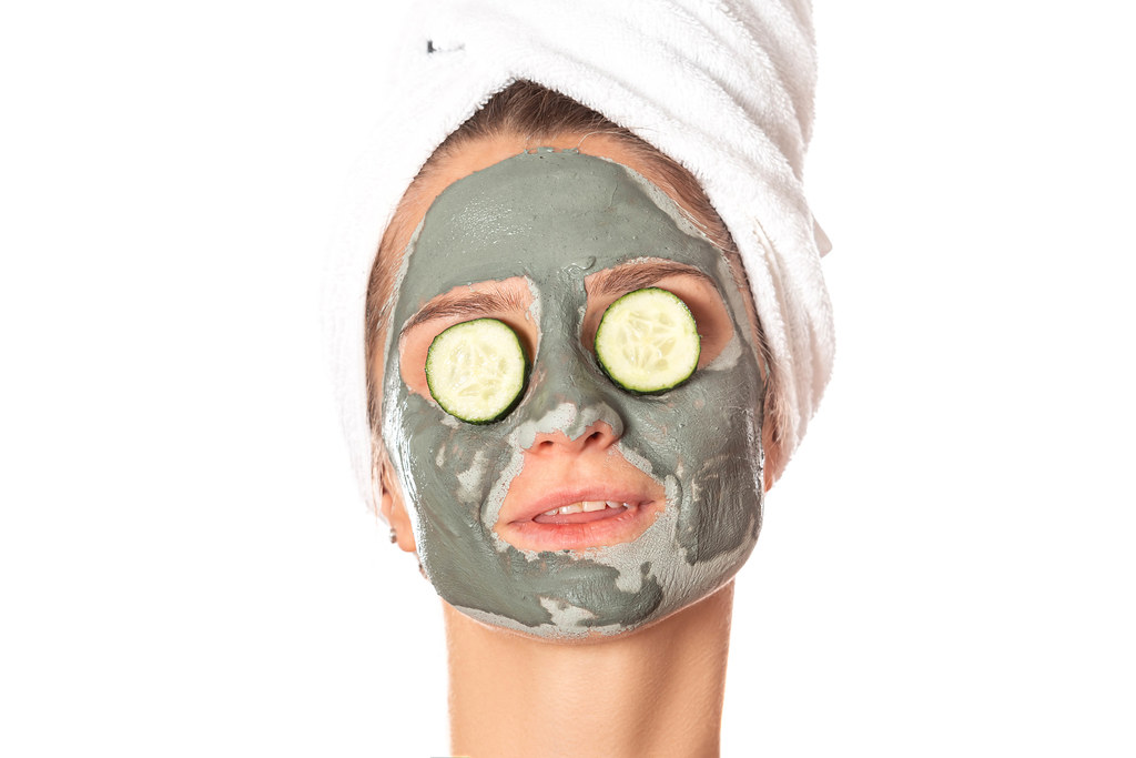 Young woman with a clay mask, covering her eyes with cucumbers on white background