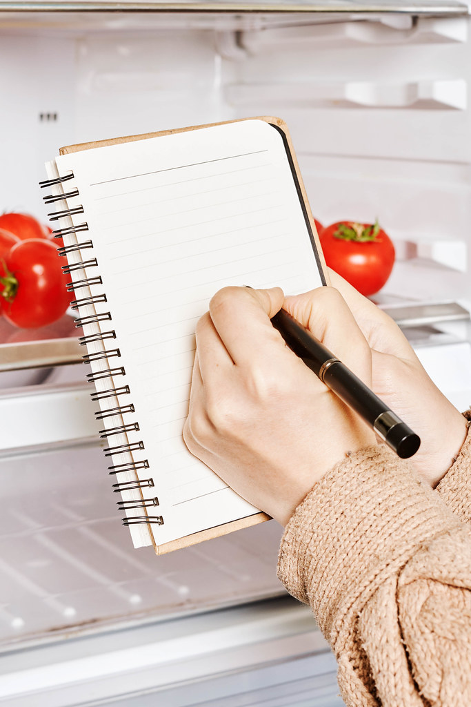 Young woman writing shopping list near the open refrigerator
