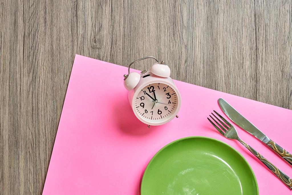 Zeit für Mittagspause: grüner Teller, Besteck, Wecker und rosa Tischset auf einem hölzernen Tisch