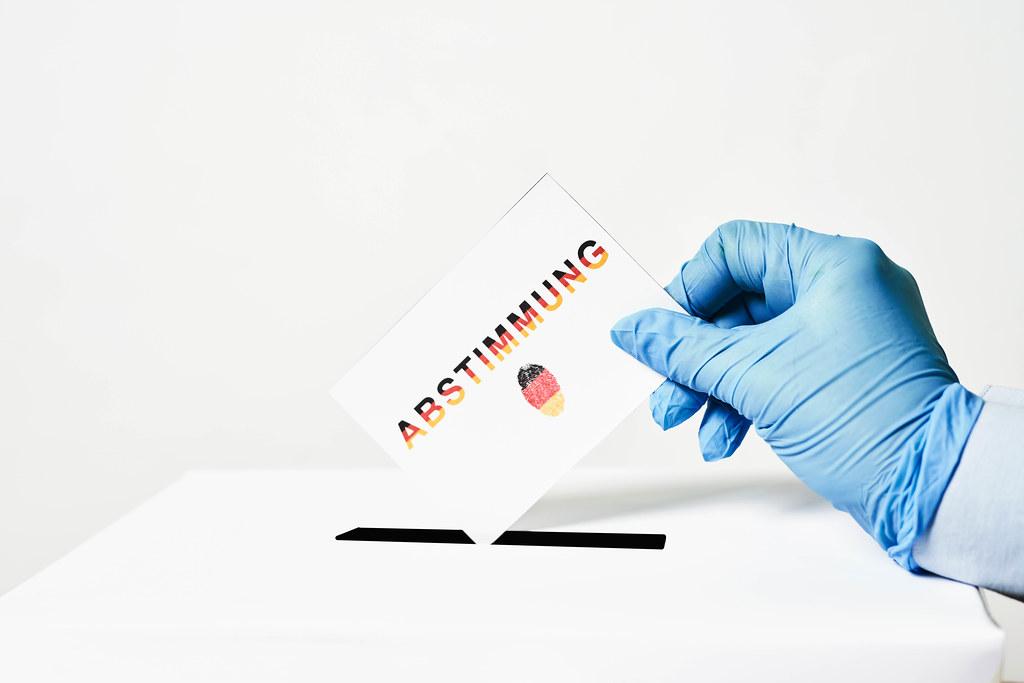 """Zettel mit Schrift """"Abstimmung"""" und Fingerabdruck in den Farben der deutschen Flagge in der Hand eines Wählers"""