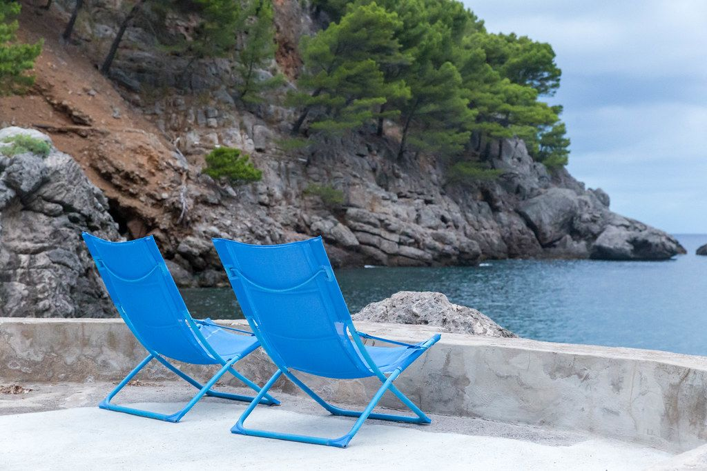 Zwei blaue Liegestühle vor der ruhigen Bucht von Port de Sa Calobra, Serra de Tramuntana, Mallorca
