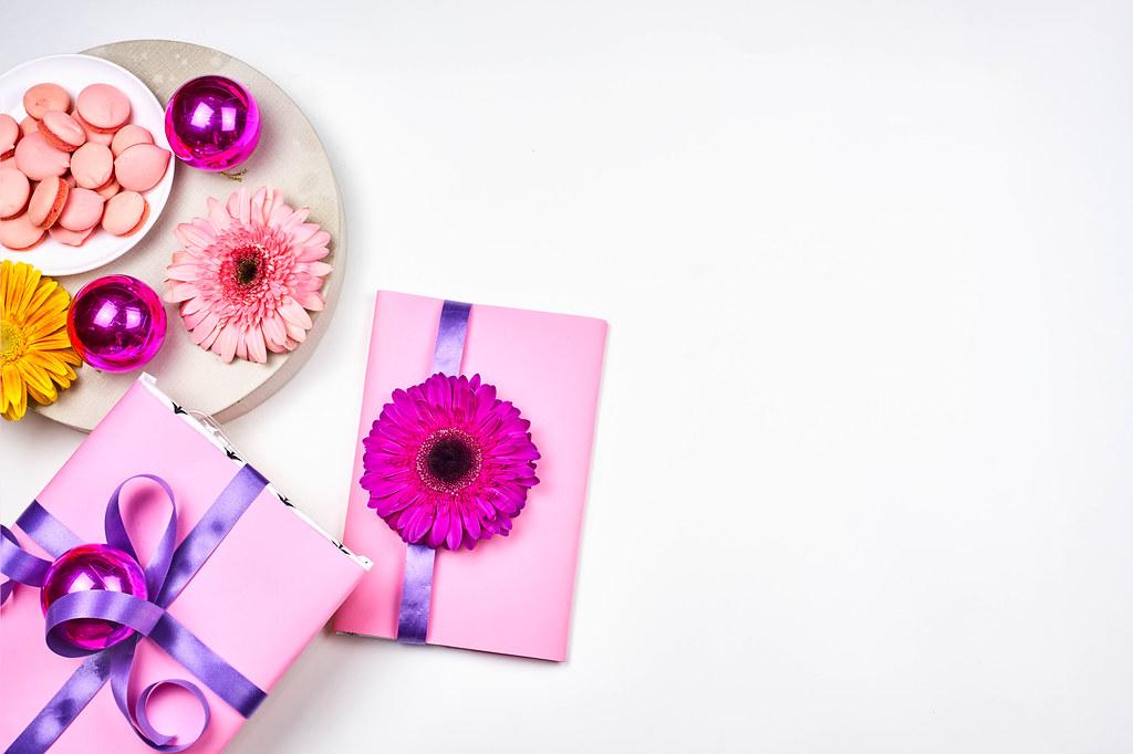 Zwei Geschenke in Rosa gepackt und Party-Deko. Weißer Hintergrund mit Platz für Text rechts