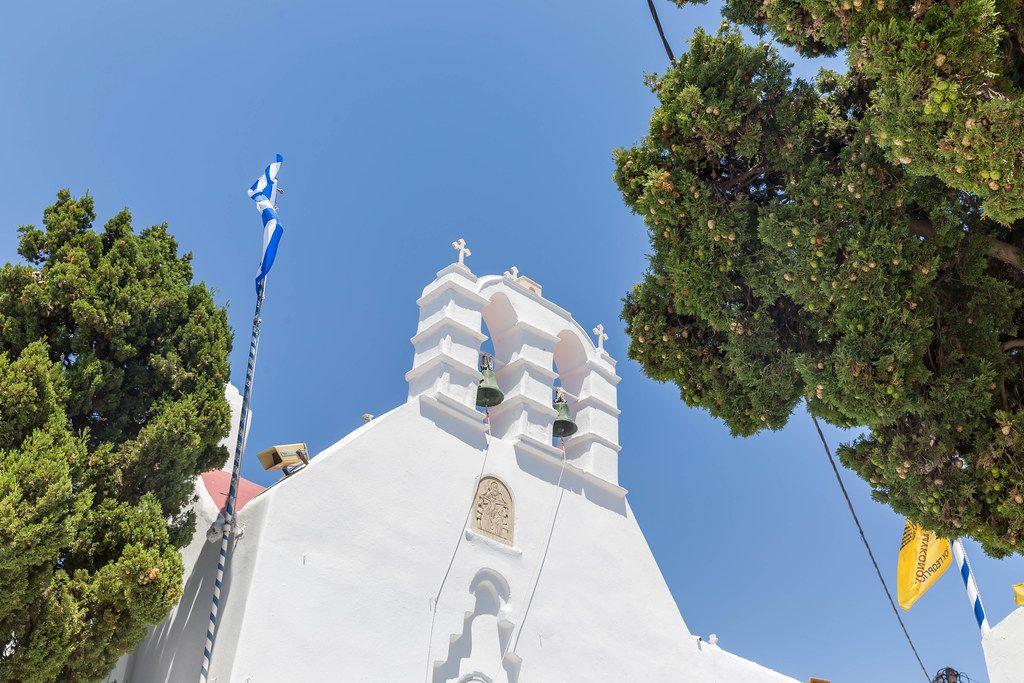Zwei Glocken, griechische Fahne, Bäume und blauer Himmel. Kirche auf Mykonos