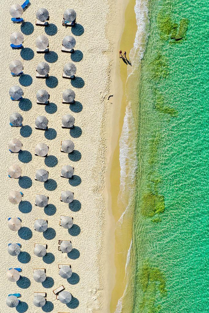 Zwei Menschen laufen den Sandstrand entlang. Drohnenaufnahme mit Strandschirmen auf Naxos