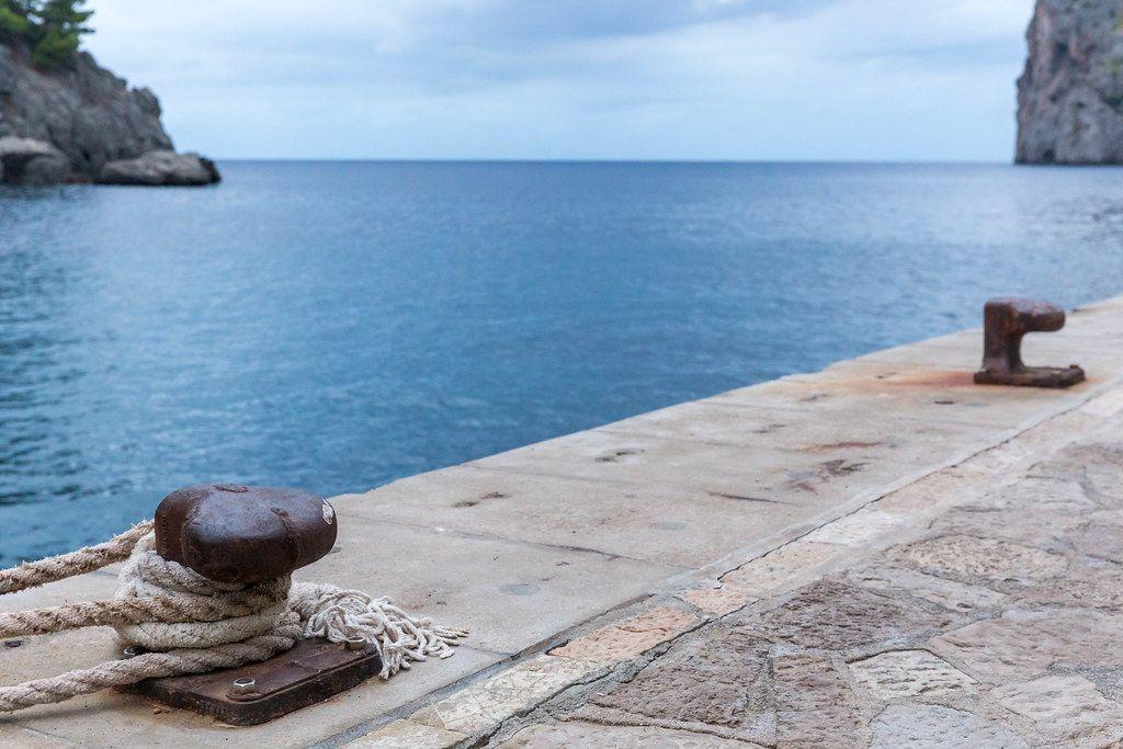 Zwei Poller für Boote und das blaue Meer am kleinen Hafen von Port de Sa Calobra auf Mallorca
