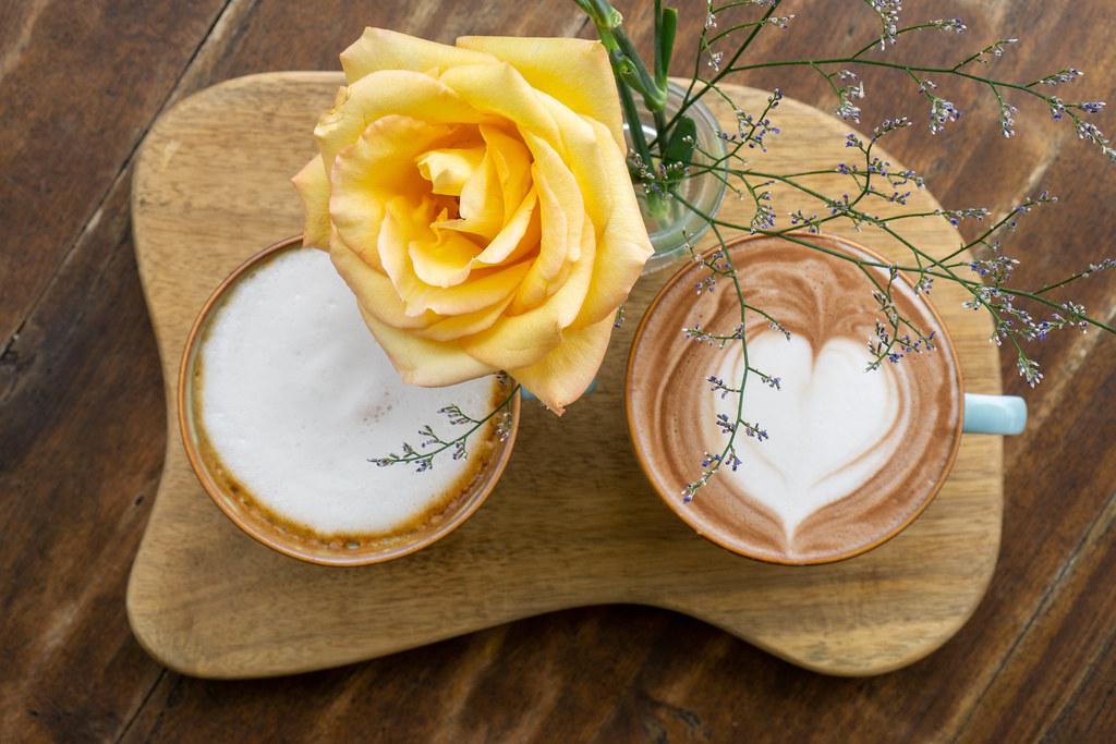 Zwei Tassen mit heißer Schokolade und Cappuccino mit Latte Art Herz von oben auf einem Holzbrett mit Blume fotografiert