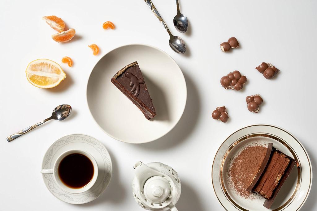 Zwei Teller mit jeweils einem Tortenstück, eine Tasse Kaffee, Schokolade, Zitrone, Mandarine, Kanne, Löffel
