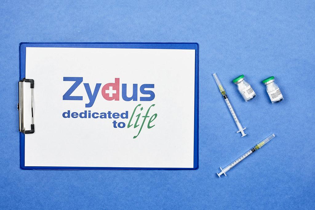Zydus Cadila vaccines with syringes on blue background