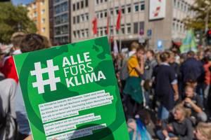 #AllefürsKlima Plakat mit den Klimademonstranten im Hintergrund