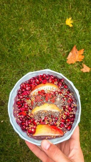 (Granat)apfel mit Chia- und Leinensamen auf einer Eiweiß-Acai-Mischung
