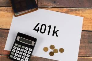 """""""401 k""""  auf weißem Papier geschrieben, neben einem Taschenrechner, Kleingeld aus Eurocent-Münzen und einer Geldbörse"""