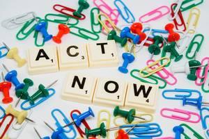 """""""Act Now"""" -Handel jetzt Schriftzug mit Scrabblesteinen, umgeben von bunten Reißzwecken und Büroklammern"""