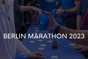 """""""Berlin Marathon 2023"""" -Bildtite, vor Sportlern am blauen Adidas-Infostand"""