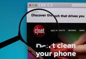 """""""Cnet"""" Schriftzug und Logo, durch eine Lupe betrachtet"""