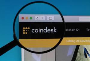 """""""Coindesk"""" Schriftzug und Logo, vergrößert durch ein Lupenglas dargestellt"""