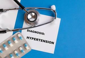 """""""Diagnose: Bluthochdruck"""", geschrieben auf blauem Ärzteordner, neben Medikamenten und Stethoskop"""
