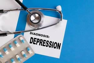 """""""Diagnose: Depression"""", geschrieben auf blauem Ärzteordner, neben Medikamenten und Stethoskop"""