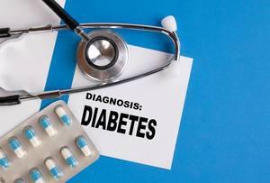 """""""Diagnose: Diabetes"""", geschrieben auf blauem Ärzteordner, neben Medikamenten und Stethoskop"""