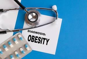 """""""Diagnose Fettleibigkeit"""", geschrieben auf blauem Ärzteordner, neben Medikamenten und Stethoskop"""