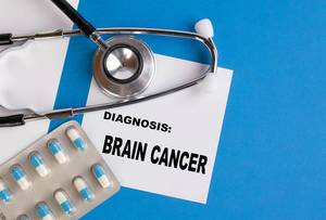 """""""Diagnose: Hirntumor"""", geschrieben auf blauem Ärzteordner, neben Medikamenten und Stethoskop"""