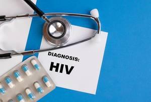 """""""Diagnose: HIV"""", geschrieben auf blauem Ärzteordner, neben Medikamenten und Stethoskop"""