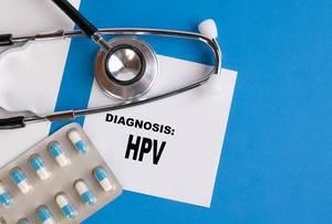 """""""Diagnose: HPV"""", geschrieben auf blauem Ärzteordner, neben Medikamenten und Stethoskop"""
