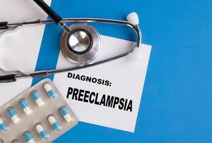 """""""Diagnose Präeklampsie"""", geschrieben auf blauem Ärzteordner, neben Medikamenten und Stethoskop"""