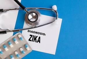 """""""Diagnose Zika"""", geschrieben auf blauem Ärzteordner, neben Medikamenten und Stethoskop"""
